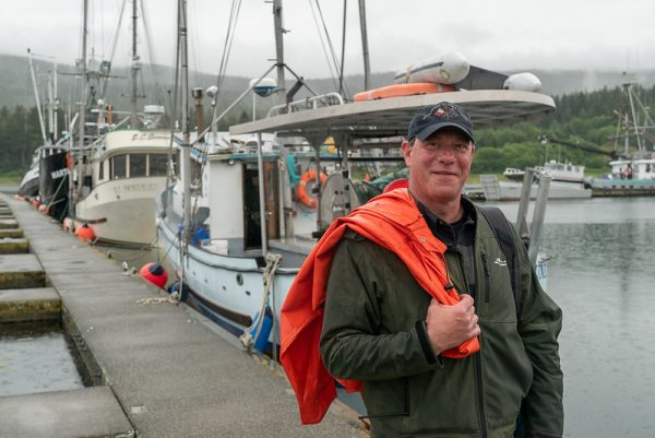 Al Gross stands on a boat dock holding fisherman's jacket over his shoulder, looking at the camera