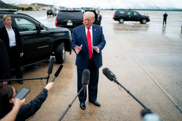 Donald Trump, wearing a black suit and dred tie, gestures in a rainy lot next to several black SUVs with microphones visible in the foreground