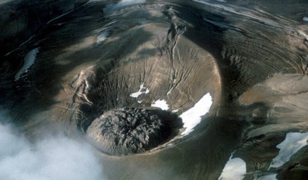 An aerial view of a crater with an  unusual rock formation in the middle that looks like oozing lava