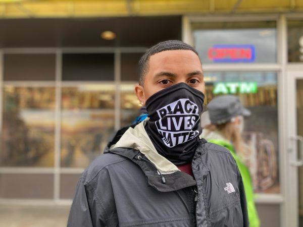 "A portrait of a young Black man wearing a mask that says ""Black Lives Matter"""