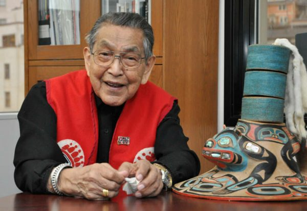 An elder Alaska Native man in a red vest smiles while sitting at a table
