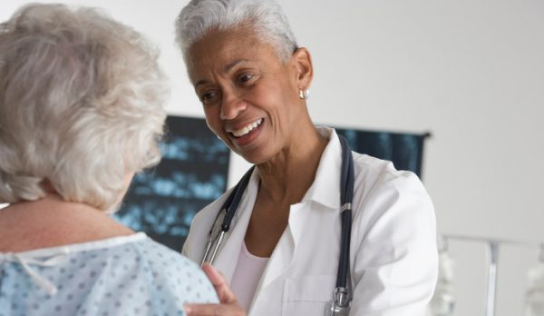 Female physician speaks with elderly woman