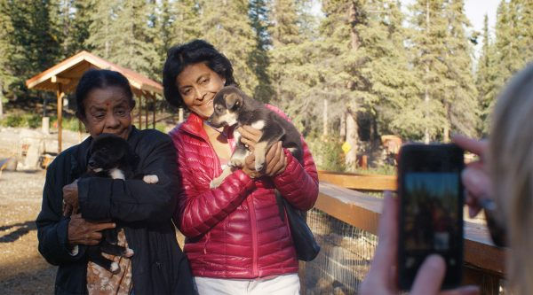 Two women hold puppies and pose for a smartphone photo in front of spruce trees