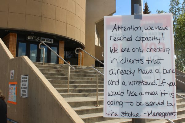 """A sign in front of a beige entry way behind grey steps reads Attention, we have reached Capacity"""""""