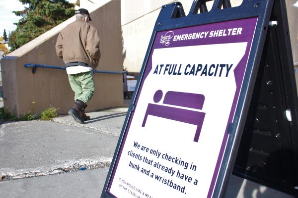"A purple fold-out sign with the words ""Full Capacity"". Behind it, a man in a tan jacket descends a ramp"