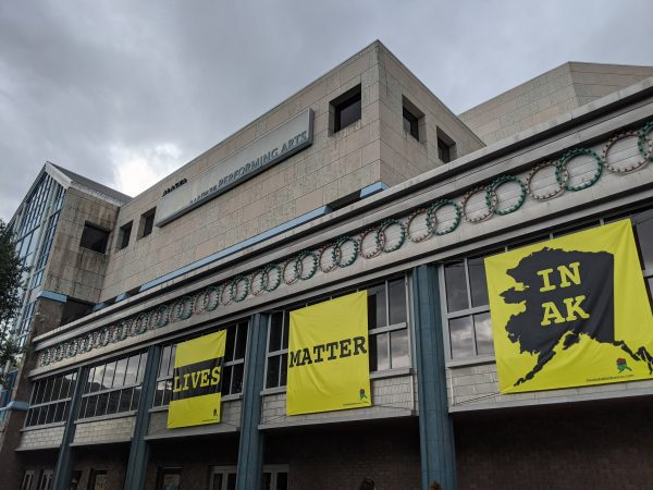 "Three yellow banners affixed to the side of the building that read ""Lives,"" ""Matter,"" and ""In AK"""