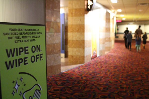 """a sign that says """"Wipe on Wipe off"""" in the corridor leading to the movie theater. A family walks at the end."""