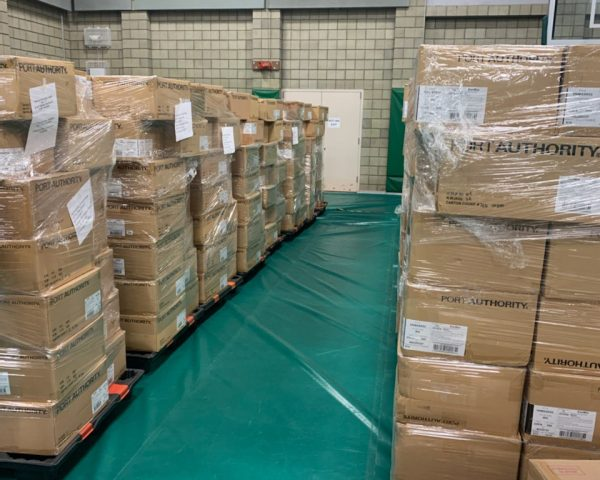 Dozens of cardboard boxes containing cloth masks are stacked on pallets inside a warehouse.