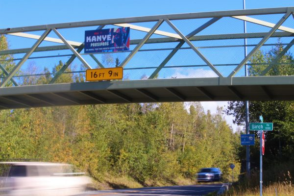 A blue Kanye sign hangs on an elevated footbridge as two cars pass