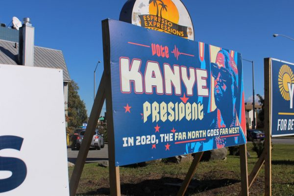 A Kanye sign next to two other political signs with a sign for Espresso Expressions in the background