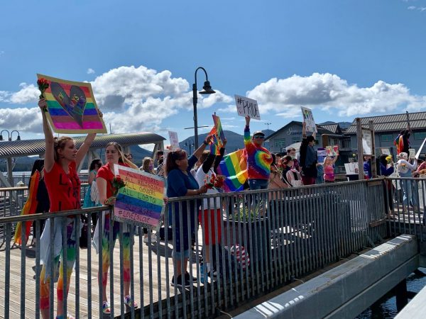 Supporters wave signs on a bridge on a sunny day. Many are wearing tie dyed shirts and rainbow colors.