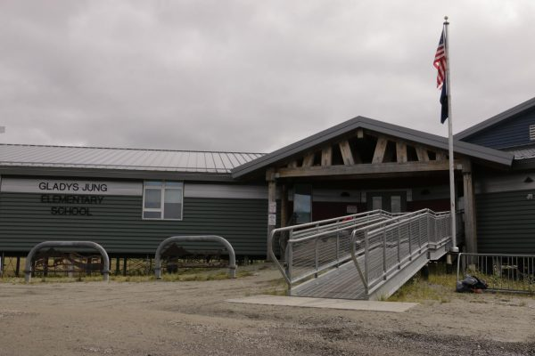 A green school with metal siding and a walkway leading to the front door.