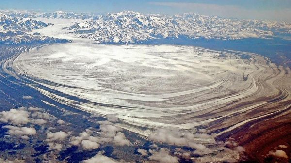 A glacier seen from the air with large bowed striations coing out iniot ht ebay