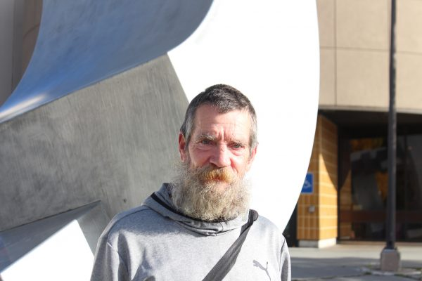 A white man in a grey hoodie and a greying beard stands in front of a stainless steel sculpture.