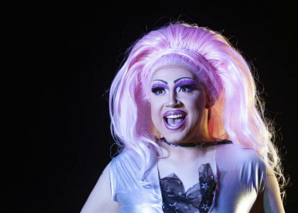 A man dressed in extravagant drag costume and pink wig sings on stage at a drag show
