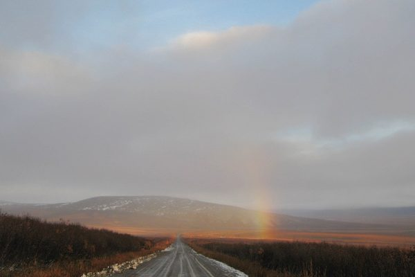 A rainbow above a gravel road with mountains in the background