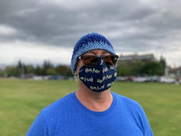 Portrait of a middle-aged white man man in a field wearing a blue beanie, sunglasses, and a mask with Harry Potter patterned across it
