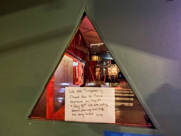 A triangular window into a bar with a sign posted outside about a closure.