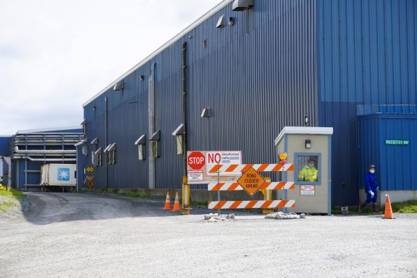 A blue warehouse building with a small entry building oustdie where employees in hazmat equiipment wait