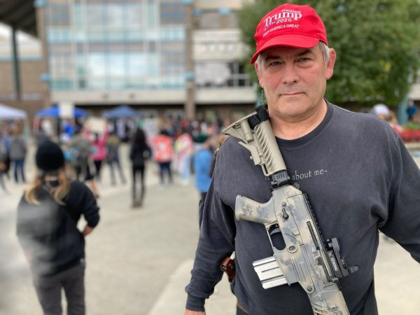 Portrait of a white older man wearing a red Trump hat with a rifle slung across his chest