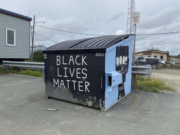 A dumpster with Black Lives Matter ppaitned on the front in white letters