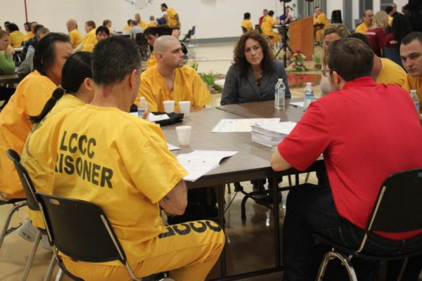 A half dozen inmates in yellow suits sit at a table with a brown haired woman in her forties wearing a blacck suit