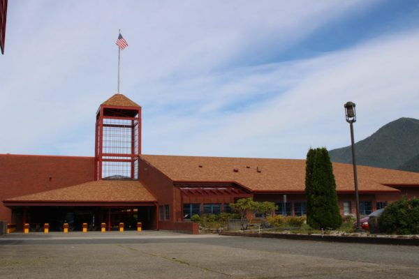 A rid school building with an american flag on top