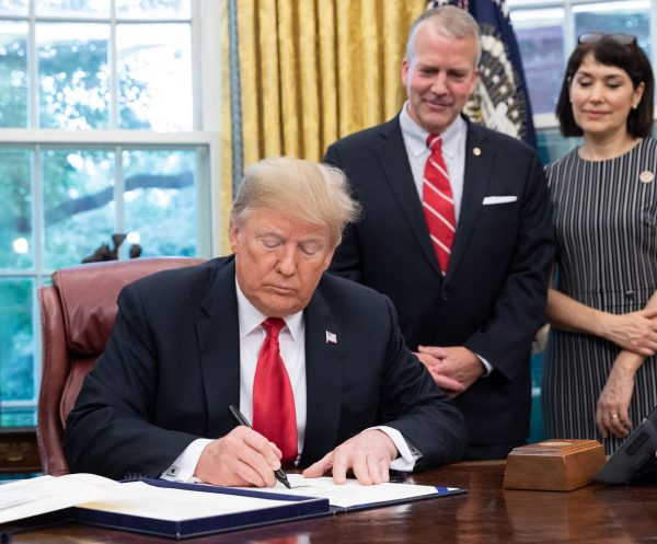 Trump sits at a desk, signing paper. A man and a woman stand behind him