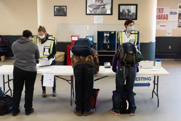 Seen frm behind, three travelers fill out forms in front of  a white fold out table manned by two workers