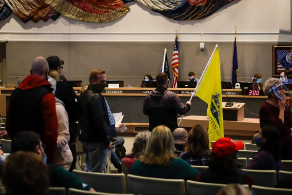 People line up to provide public testimony at the Anchorage Assembly meeting.