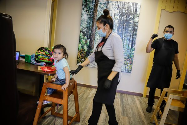a woman helps her child in a high chair and a man signals for something in the kitchen