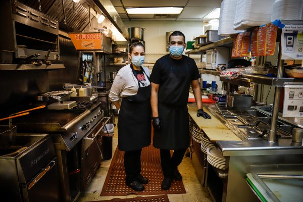two people stand in a restaurant kitchen