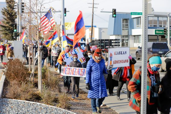 a group of people marching and holding signs and flags