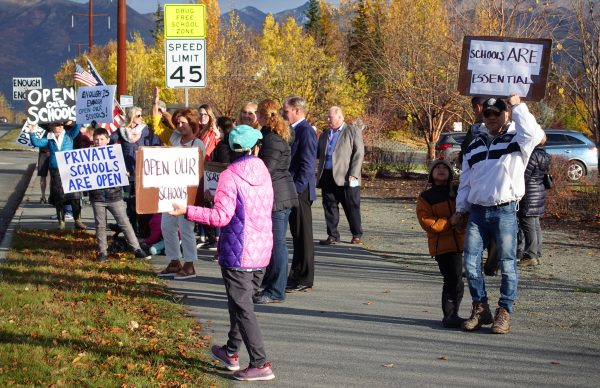"Protesters gather on the sidewalk in Anchorage with signs that read ""Schools ARE Essential"" and ""Open our schools!"""