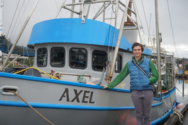 "A white woman in a blue best poses next to a light blue boat with teh name ""Axel"""