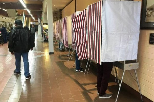 Voters mark their ballots in a long hallway