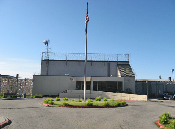 A plain looking building with a flag pole in front
