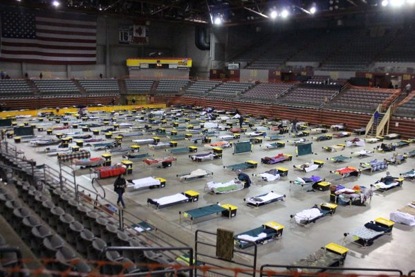 As seen from the mezanine, about a hundred cots are spread on the floor of a stadium.