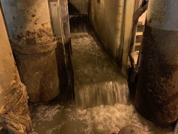 Murky water runs throuogh a channel