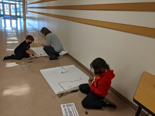 Two students and a teacher code small robots by marking colors on a piece of paper in a hallway in an elementary school