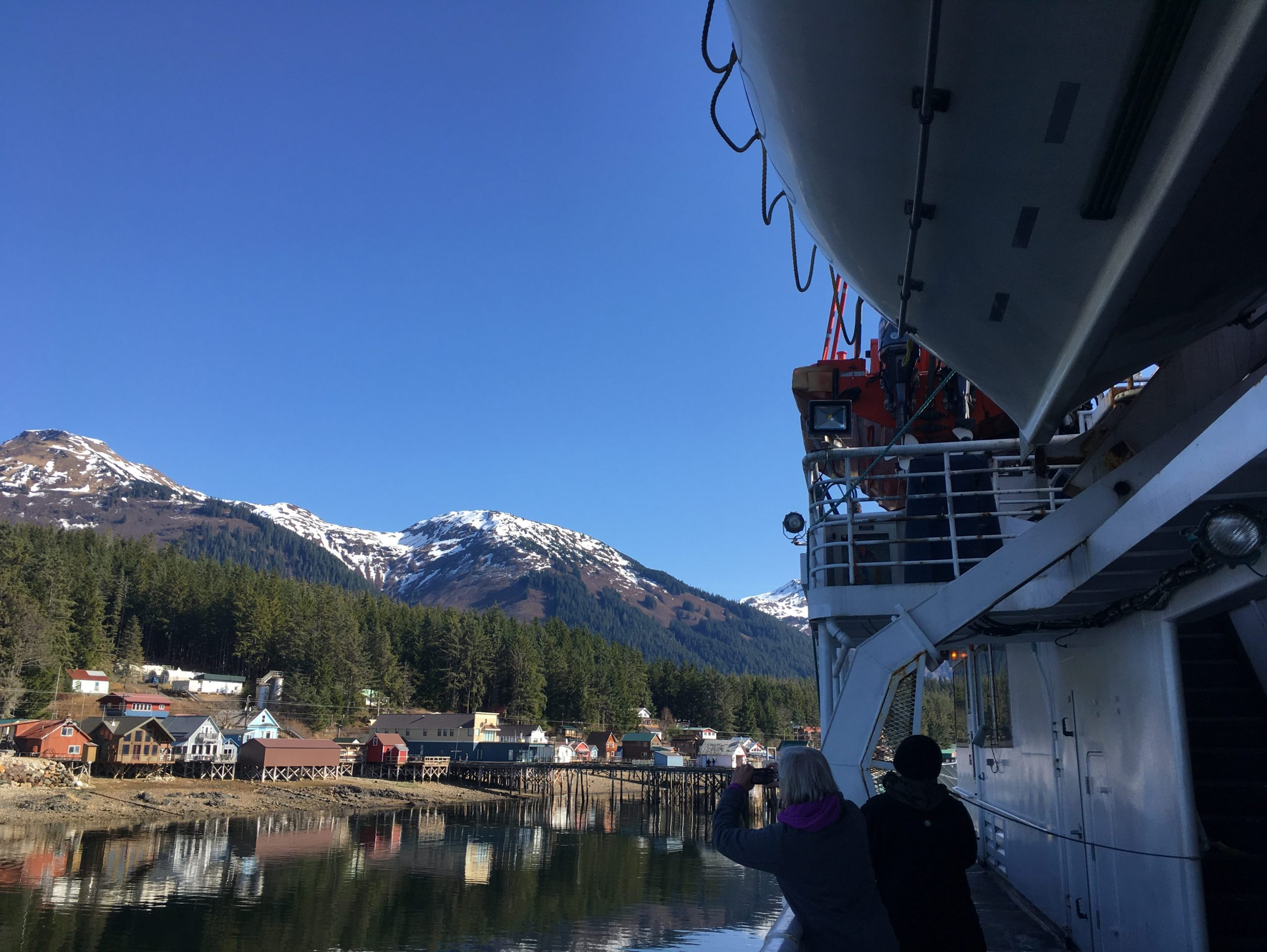 A ferry approaches a town next to spruce covered mountains