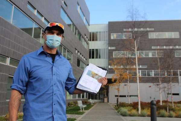 A man in a blue button up shirt, black baseball cap, and sunglasses, holds a piece of paper with photos of an apartment.