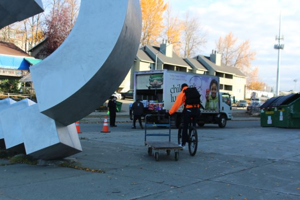 A man in an orange sweatshirt pulls a cart while riding his bicycled. Workers unload a truck in the background.