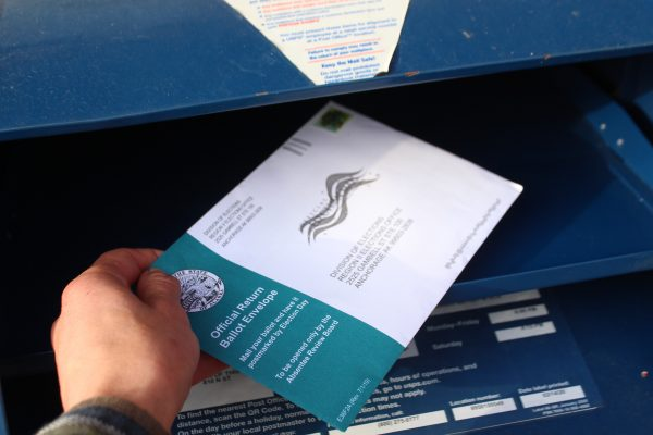 An envelope with a division of elections address is placed in a mailbox