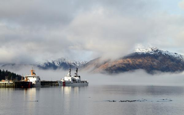 A coast guard cutter mooring at a dock with  mountains in the background