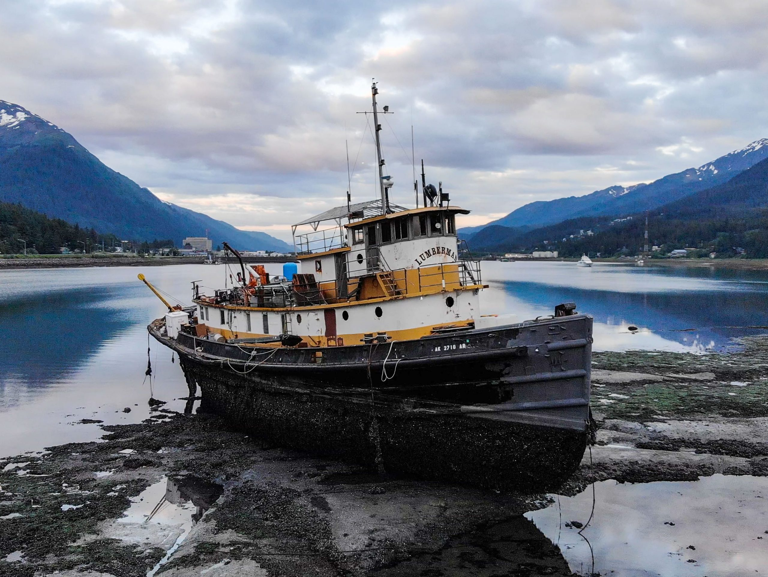 A weathered greyissh tugboat on the sandy beach with mountains in the background