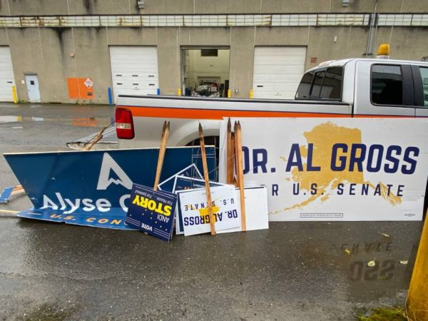 Campaign signs rest upside down against a white pickup truck