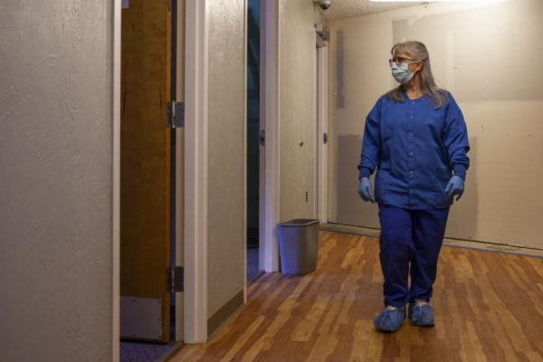 A white woman in a blue suit walks through a hallway looking into one of the rooms