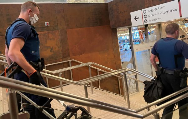 Two white police officers walk dodwn a marble staircase with brushed silver railings