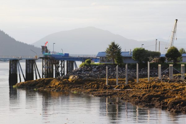 An empty ferry terminal on a foggy day with mountains in the background